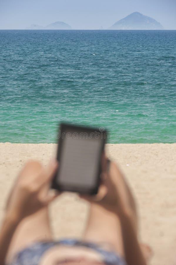 Leggendo dal e-lettore che si rilassa sulla spiaggia fotografia stock libera da diritti