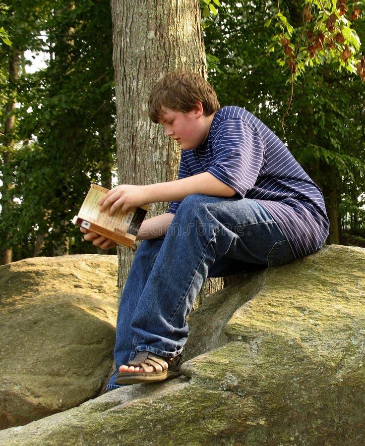 Leggendo sulla roccia fotografie stock libere da diritti