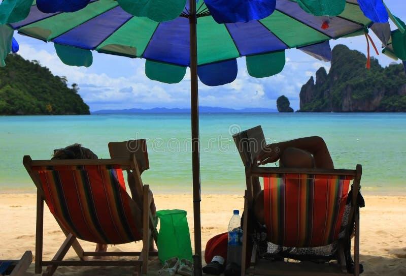 Leggendo sulla spiaggia immagini stock