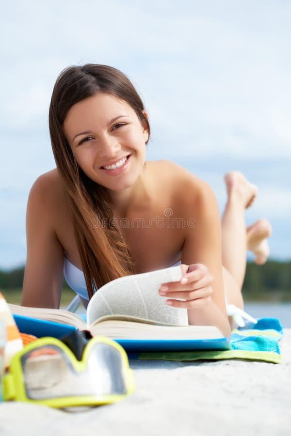 Leggendo sulla spiaggia immagine stock libera da diritti