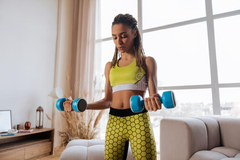 Woman wearing yellow leggings and top holding barbells royalty free stock photos