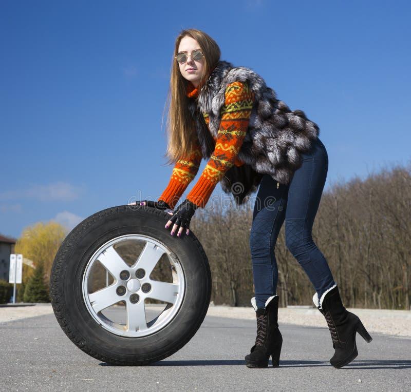 Leggy beautiful female holds big wheel royalty free stock photos