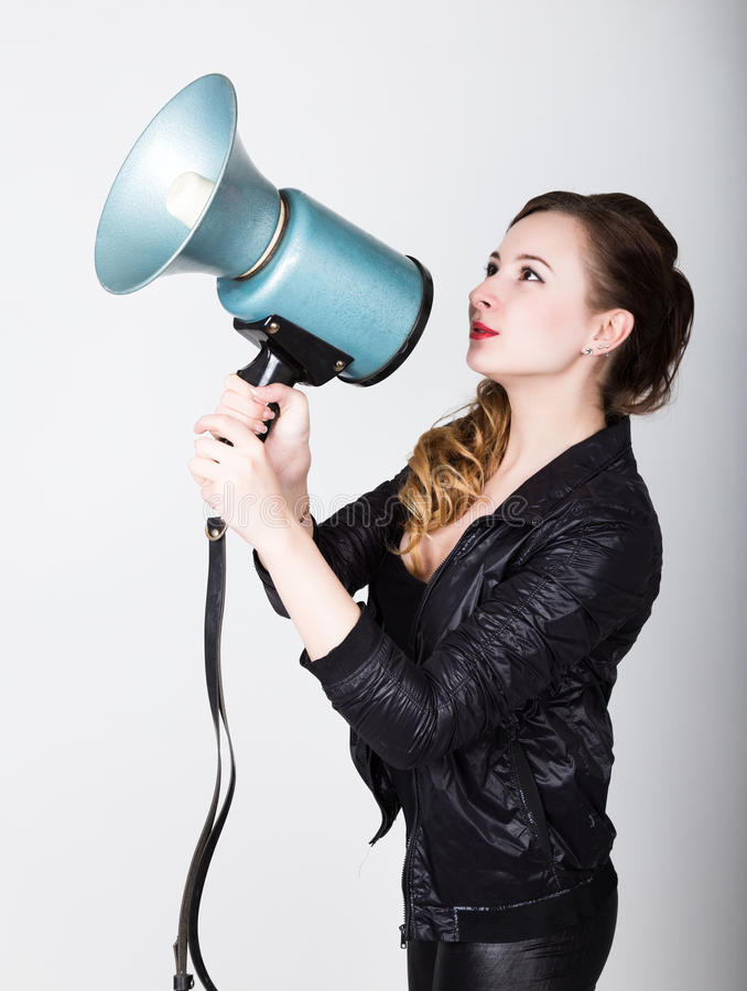 Leggy beautiful girl in black skin-tight trousers and jacket, she yells into a bullhorn. Public Relations.  stock photography