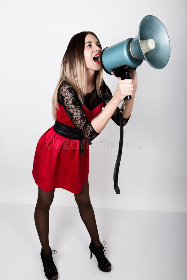 Leggy beautiful girl in a red dress with lace sleeves, she yells into a bullhorn. Public Relations.  stock photos