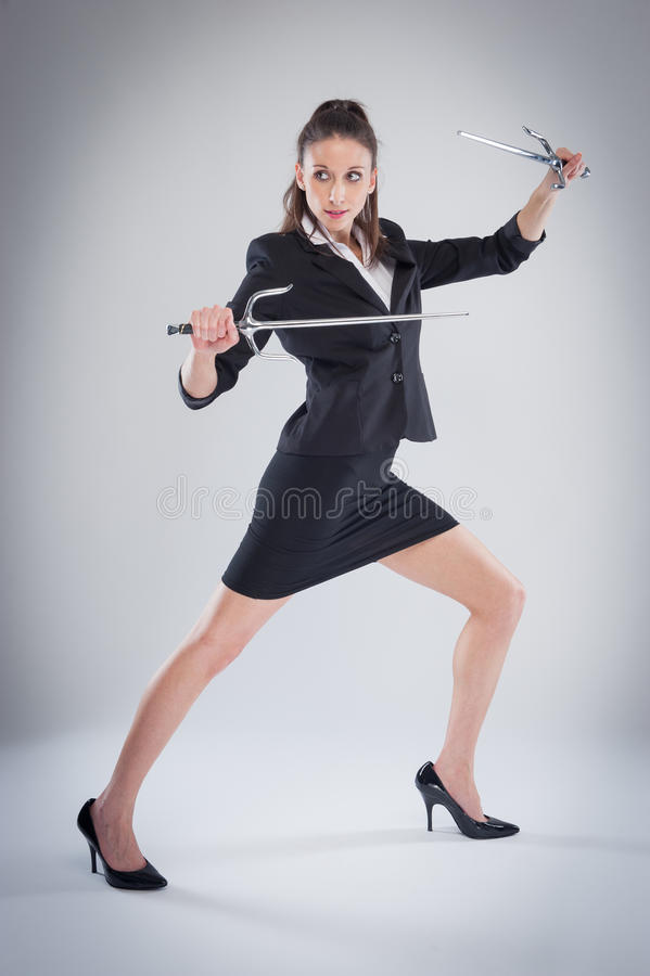 Leggy Woman Posing with Martial Arts Swords. Woman in black suit means business royalty free stock image