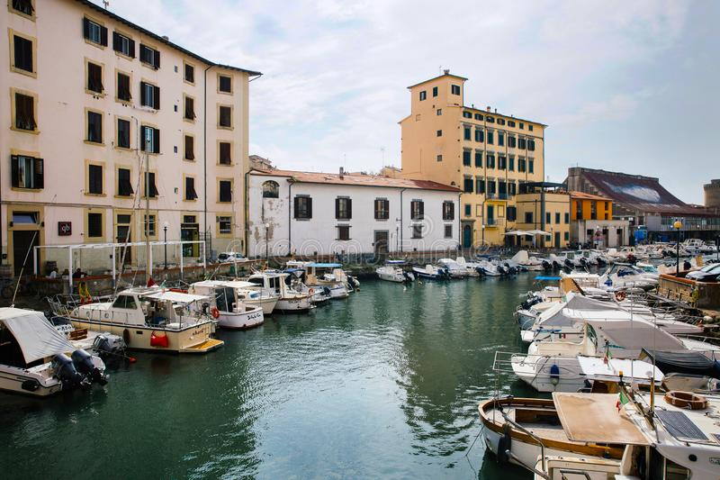 LEGHORN, ITALY - OCTOBER 3, 2017: Boats moored on canal in Venezia Nuova district of Livorno, Tuscany. Travel impressive cityscape. Postcard royalty free stock image