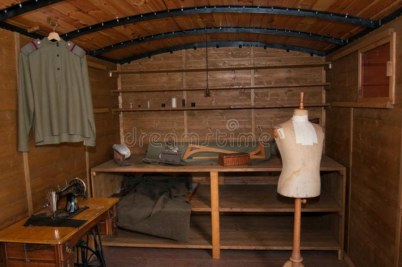 Legionary train on the road with sewing workshop. Sewing workshop in the legionary train.Standing sewing machine , figurina , iron , military blouse with tabs royalty free stock image