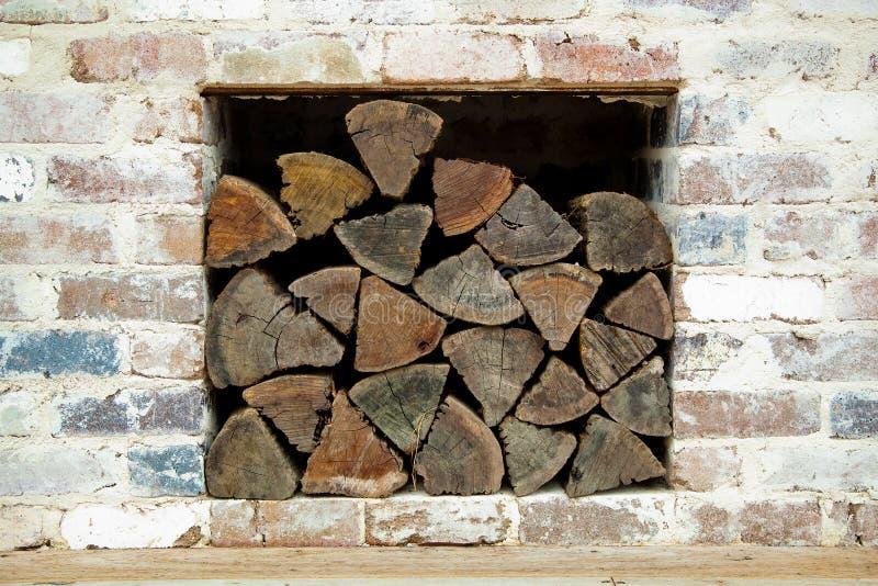 Legna da ardere rustica impilata dentro un vecchio muro di mattoni immagini stock libere da diritti