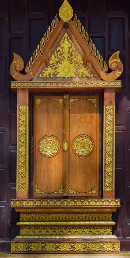 Legno che scolpisce descrizione sul tempio tailandese della cappella della finestra fotografia stock libera da diritti