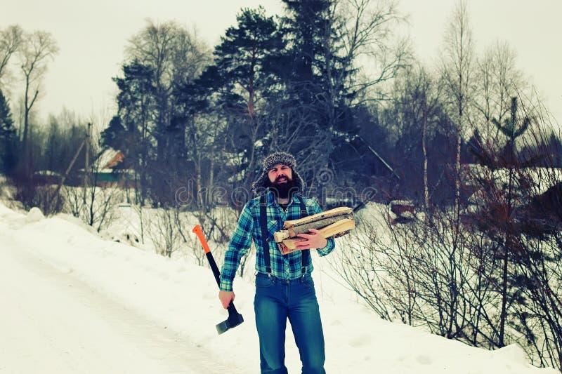 Legno dell'ascia dell'uomo di inverno immagine stock