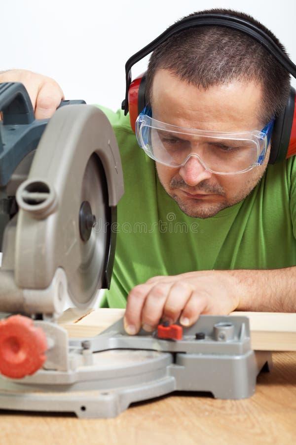 Legno di taglio dell'operaio del carpentiere fotografia stock