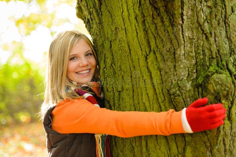 Legno sorridente di autunno dell'albero di abbraccio della ragazza dell'adolescente fotografia stock libera da diritti
