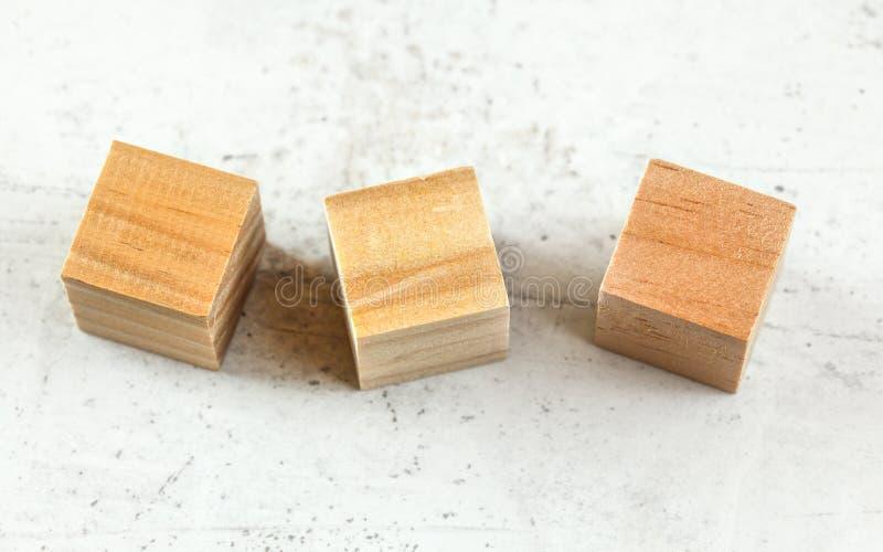 Legno vuoto tre che gioca i blocchetti del cubo sul bordo bianco immagine stock