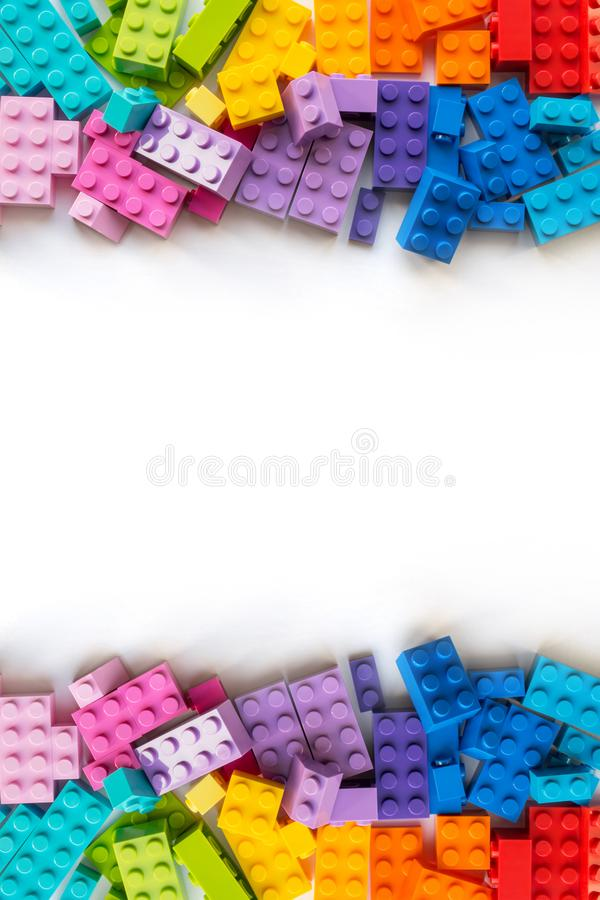 Lego background. Border of A lot of Colorful Plastick constructor bricks on white background. Popular toys. Copyspace. Vertical. A bunch of Multicolor Plastick royalty free stock images