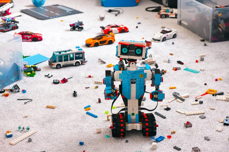 Lego BOOST robot standing on room floor with other Lego toys, bricks and baseplates stock photo