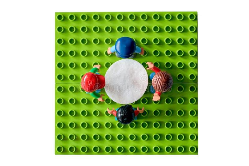 Lego folk runt om tabellen, sammanslutning från olik uppsättning fotografering för bildbyråer