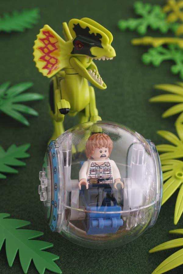 Lego Jurassic parkerar Grå minifigure i gyrosphere och dilophosau arkivfoto