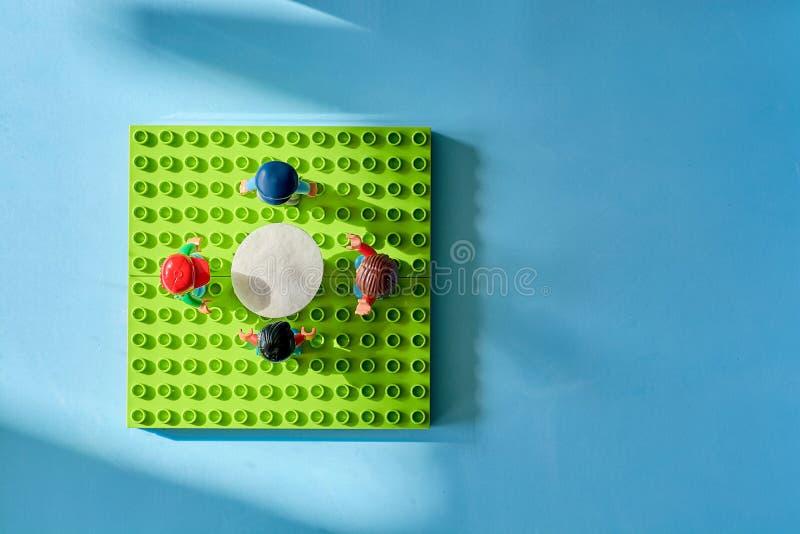 Lego-Leute um die Tabelle, Mähdrescher vom unterschiedlichen Satz stockfoto