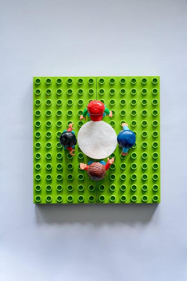Lego-Leute um die Tabelle, Mähdrescher vom unterschiedlichen Satz stockfotografie