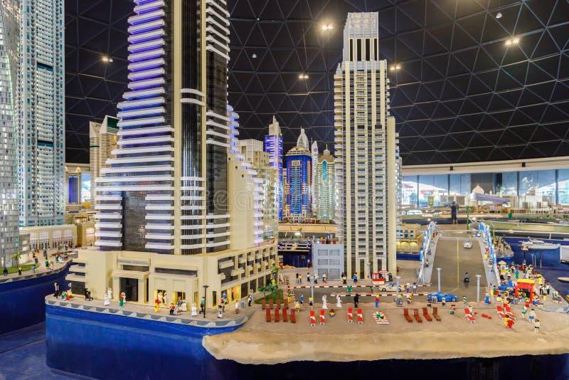 Lego-Miniaturen von den hohen Gebäuden, die auf Küstenlinie des Seeabschlusses mit dem Strand mit Leuten in Miniland von Legoland stockfotografie