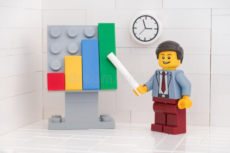 Lego minifigure businessman pointing out company growth on a chart stock photos
