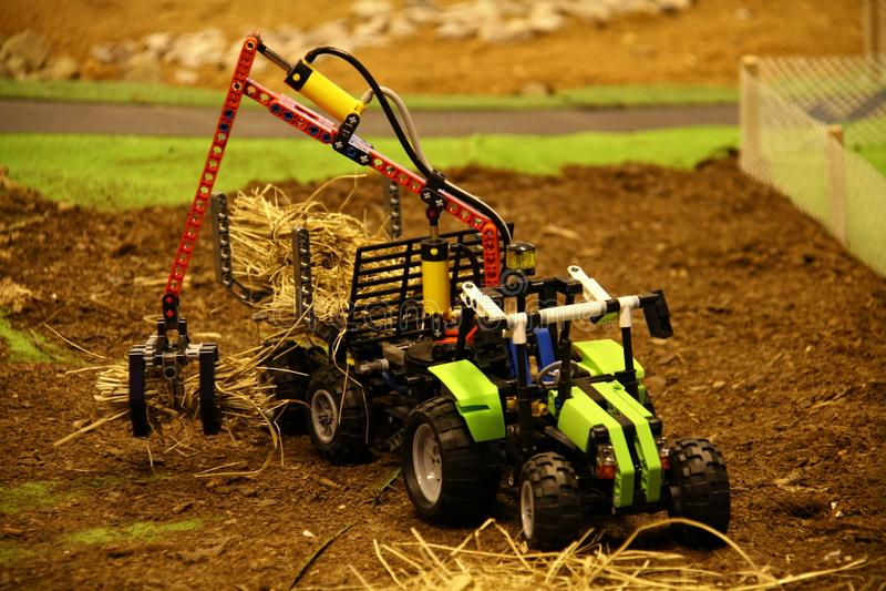 Lego modela o trator situado no ambiente do campo que pegara palhas foto de stock