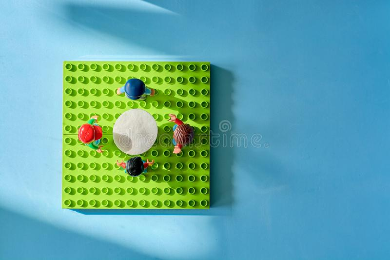 Lego people around the table, combine from different set stock photo
