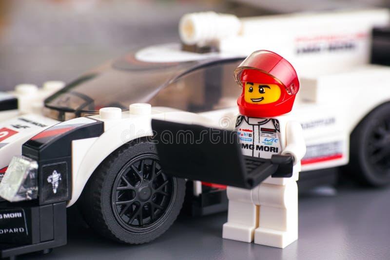 Lego prędkość Wstawia się Porsche 919 hybrydu kierowcy minifigure z laptopem blisko jego samochodu zdjęcia royalty free