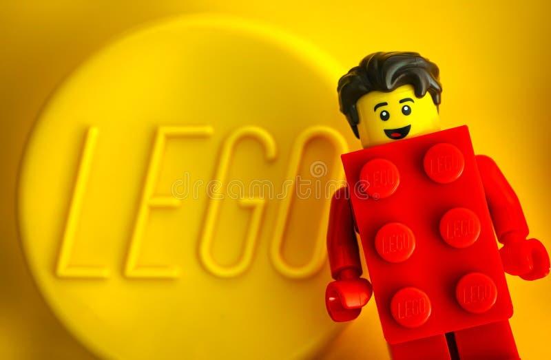 Lego Red Suit Brick Guy minifigure mot gul bakgrund med ordet LEGO royaltyfri fotografi