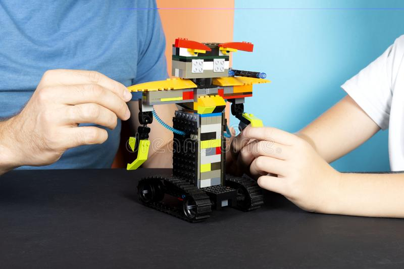 Lego robot A child and a man assemble a robot from plastic parts, train. The hottest gadgets. E-learning. Modern training stock photo