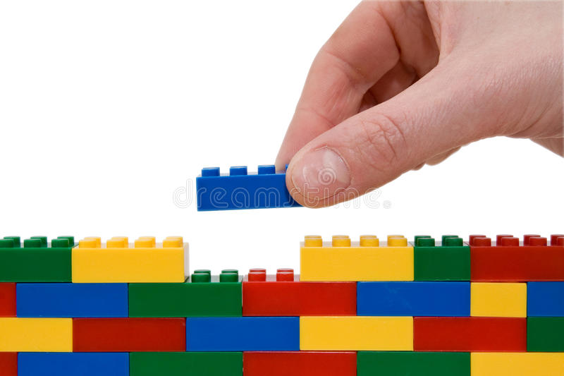 Lego wall. Hand building up a wall by stacking up lego