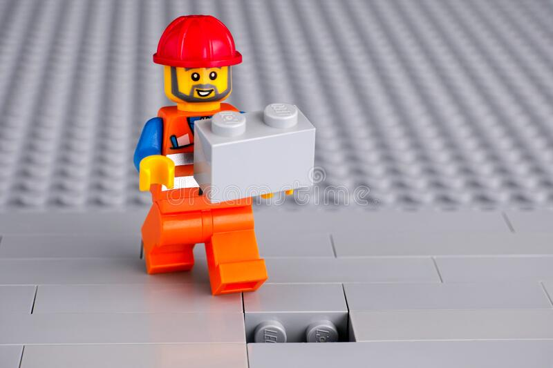 Lego worker minifigure with gray brick finishing building wall. Tambov, Russian Federation - June 06, 2020 Lego construction worker minifigure with gray brick stock photos