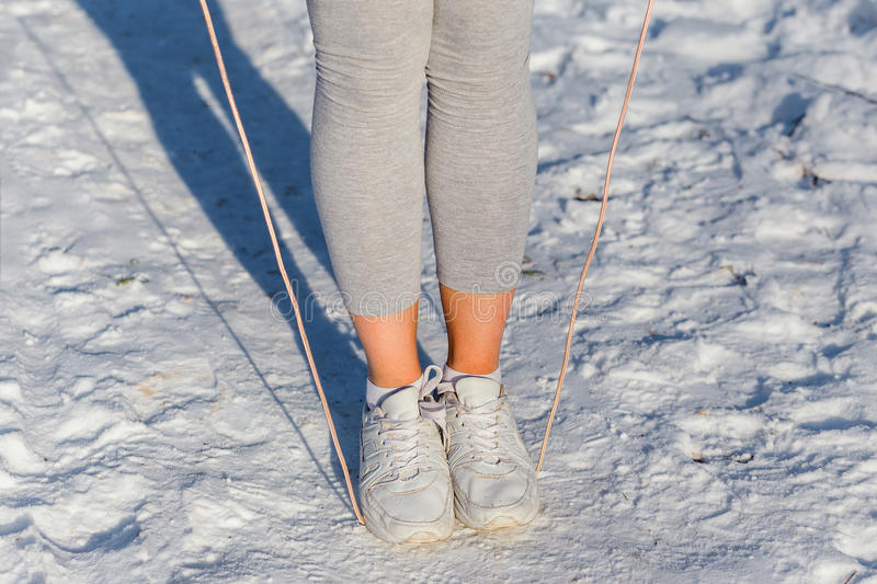 Legs of active woman with a skipping rope. In winter Park royalty free stock photos