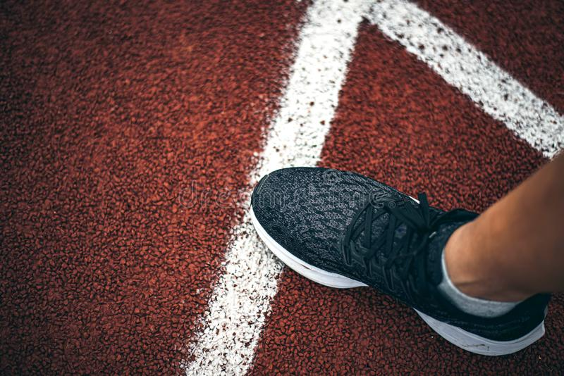 Legs of athletes wearing sports shoes on running track. Legs of athletes wearing sports shoes on white line and red running track stock image