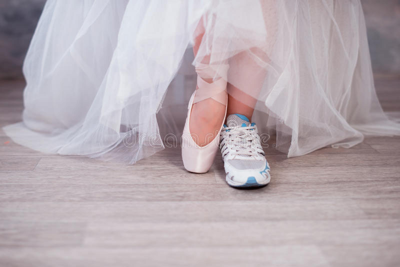 Legs of a ballerina, one foot shod in sneakers other in pointe shoes. Lifestyle, hobbies, dancing, choice stock images