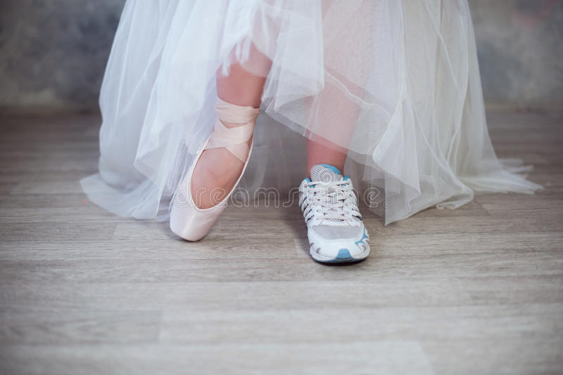Legs of a ballerina, one foot shod in sneakers other in pointe shoes. Lifestyle, hobbies, dancing, choice stock image