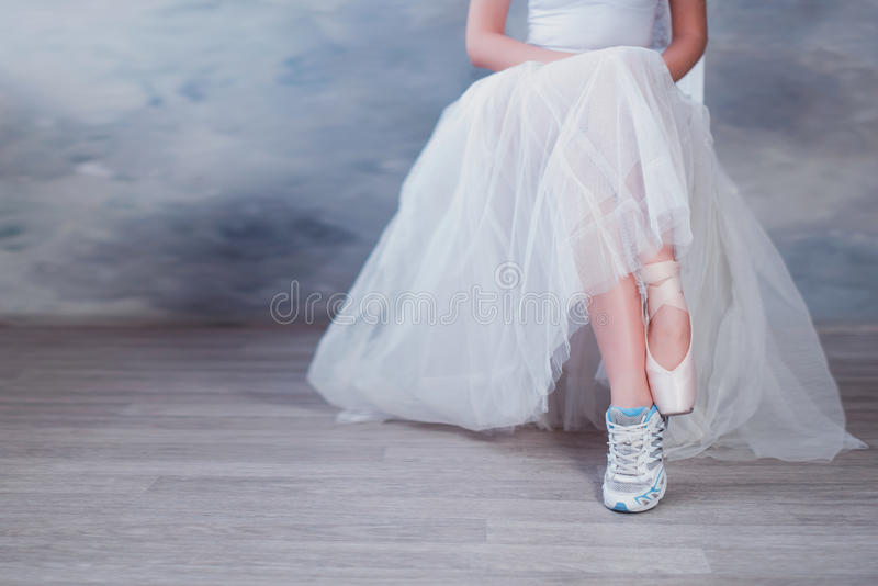 Legs of a ballerina, one foot shod in sneakers other in pointe shoes. Lifestyle, hobbies, dancing, choice royalty free stock photo