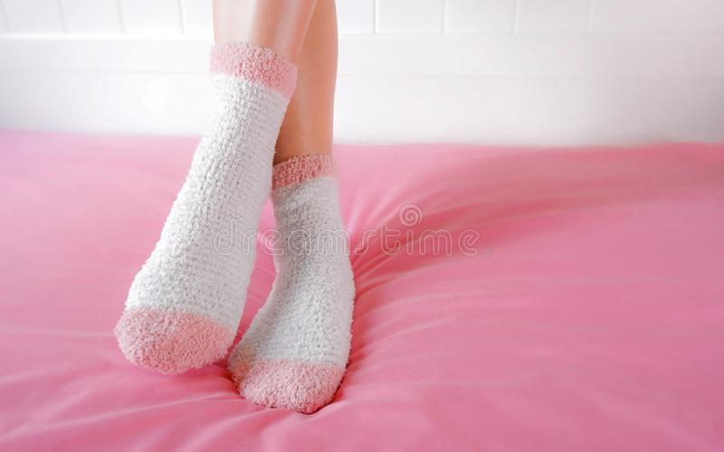 Legs of a beautiful women are wearing warm Socks on bedroom. Fashion pink Socks in cozy background. stock images