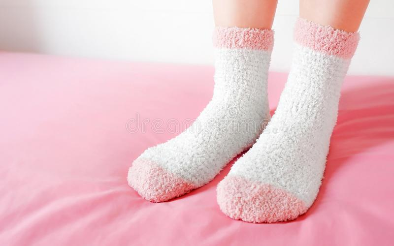 Legs of a beautiful women are wearing warm Socks on bedroom. Fashion pink Socks in cozy background. royalty free stock image