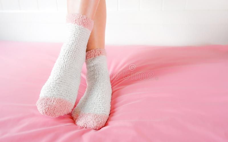 Legs of a beautiful women are wearing warm Socks on bedroom. Fashion pink Socks in cozy background stock image