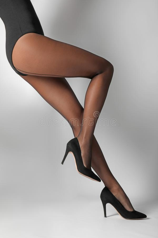Legs of beautiful young woman in black tights. On light background stock photo