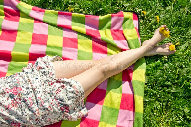 Legs of a beautiful young woman in summer dress on colorful picnic blanket royalty free stock photos