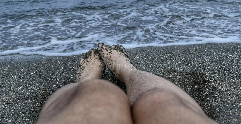 Legs in black sand, sea, and waves royalty free stock photos