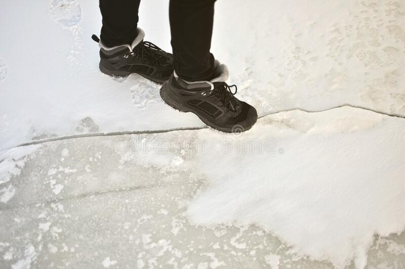 Legs in black trousers and black winter boots stand on snowy ice and point to an ice crack.  stock photography