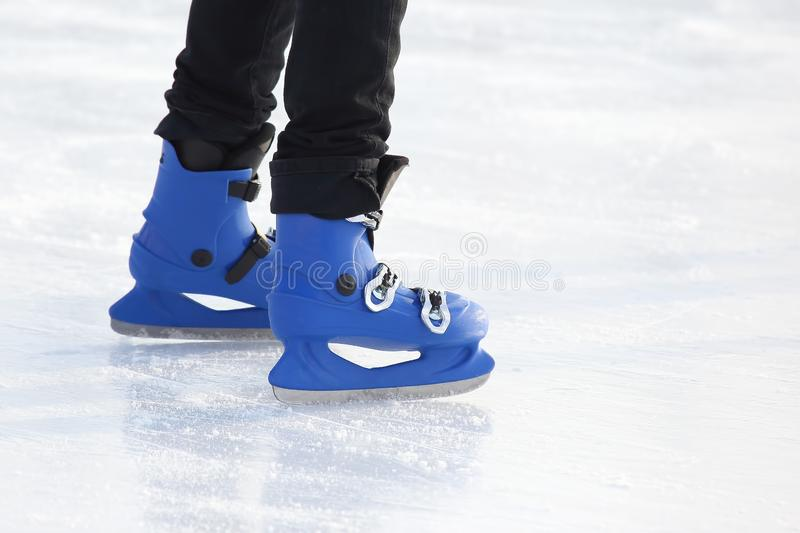 Legs in blue skating on the ice rink. The legs in blue skating on the ice rink stock image
