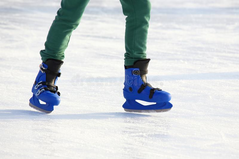 Legs in blue skating on the ice rink. The legs in blue skating on the ice rink royalty free stock photography