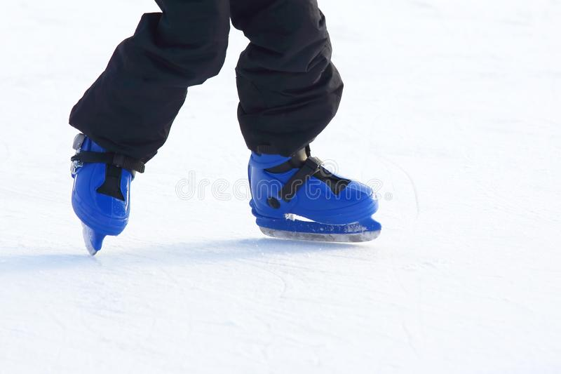Legs in blue skating on the ice rink. The legs in blue skating on the ice rink stock photos