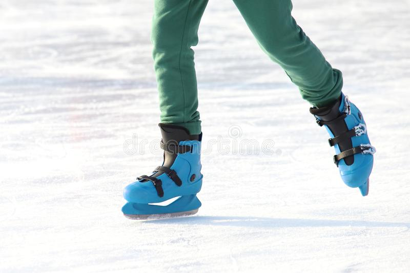 Legs in blue skating on the ice rink. sports, Hobbies and recreation of active people. The legs in blue skating on the ice rink. sports, Hobbies and recreation stock image