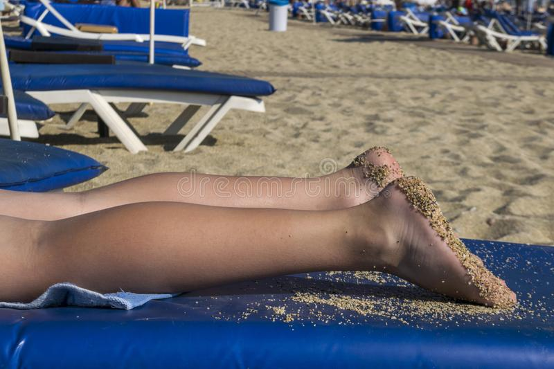 Legs on a blue sun lounger. Beach holidays. The sand on the soles of the feet. Legs on a blue chaise longue. Beach holiday. Sand on the soles of my feet. Summer royalty free stock image
