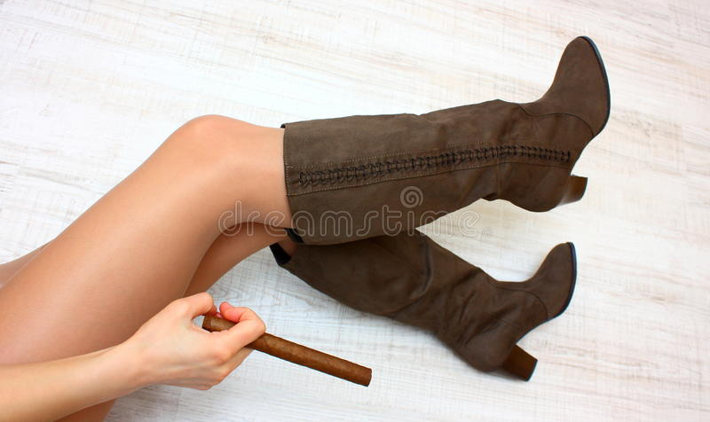 Legs, boots, and cigar stock photography